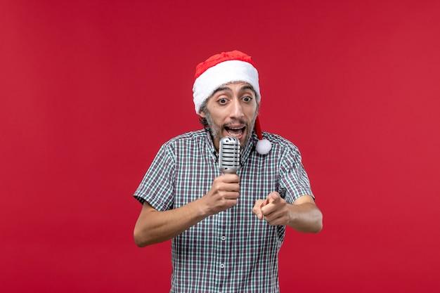 Vue de face jeune homme à l'aide de microphone sur la musique de chanteur de vacances émotion mur rouge