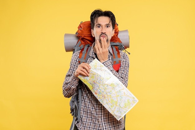 Vue de face jeune homme allant en randonnée avec sac à dos confus sur fond jaune forest company nature campus couleur carte de voyage aérien