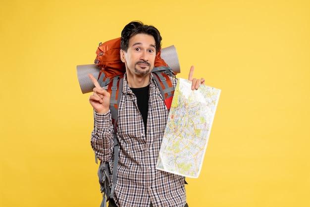Vue de face jeune homme allant en randonnée avec sac à dos tenant une carte sur fond jaune entreprise voyage air nature campus couleur