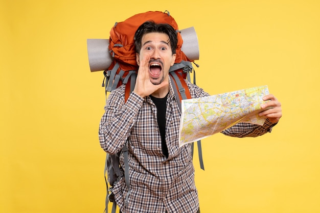 Vue de face jeune homme allant en randonnée avec sac à dos tenant une carte sur fond jaune voyage air nature compagnie campus forêt