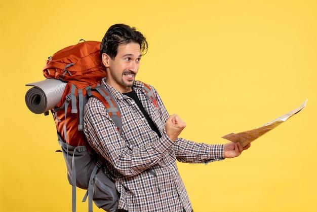 Vue de face jeune homme allant en randonnée avec sac à dos tenant une carte sur fond jaune voyage compagnie aérienne campus couleur de la forêt