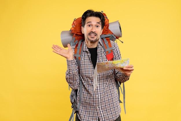 Vue de face jeune homme allant en randonnée avec sac à dos tenant une carte sur fond jaune voyage d'entreprise air nature campus forêt