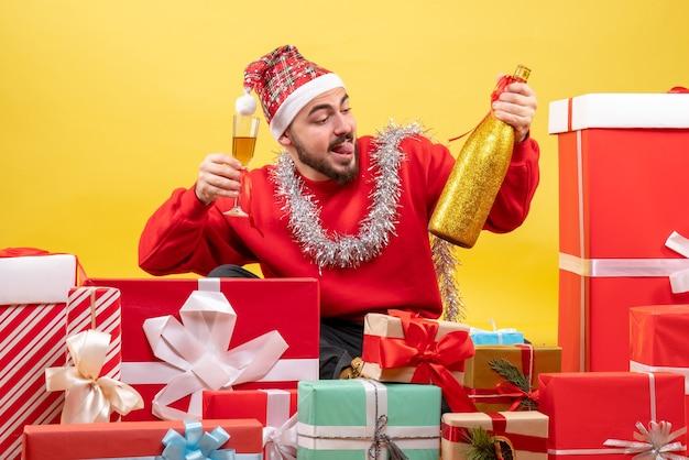 Vue de face jeune homme assis autour de cadeaux célébrant avec champagne sur fond jaune