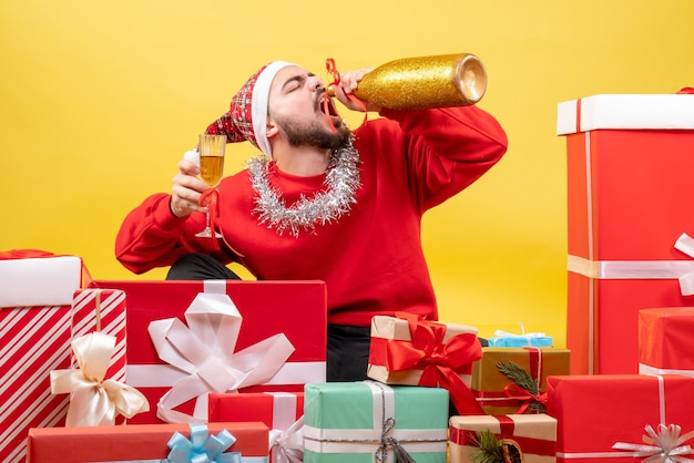 Vue de face jeune homme assis autour de cadeaux avec du champagne sur fond jaune