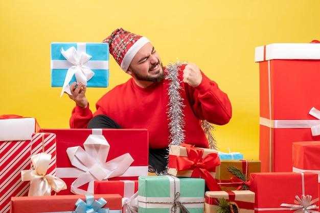 Vue de face jeune homme assis autour de cadeaux sur fond jaune