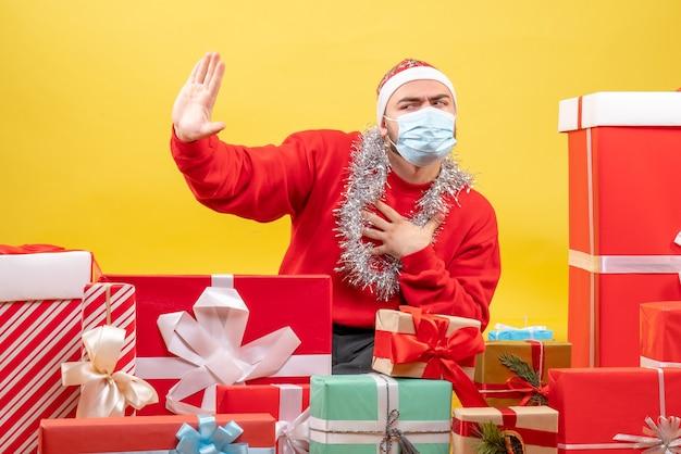 Vue de face jeune homme assis autour de cadeaux en masque sur fond jaune