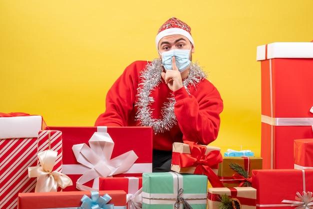Vue de face jeune homme assis autour de cadeaux en masque sur jaune