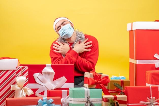 Vue de face jeune homme assis autour de cadeaux en masque stérile sur fond jaune