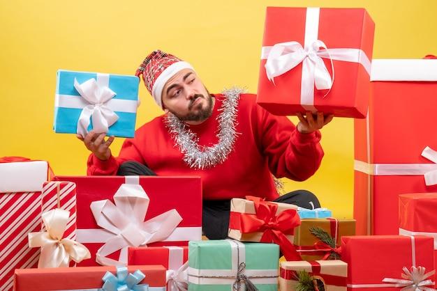 Vue de face jeune homme assis autour de cadeaux de noël sur fond jaune