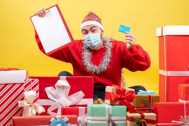 Vue de face jeune homme assis autour de cadeaux avec note et carte bancaire sur fond jaune