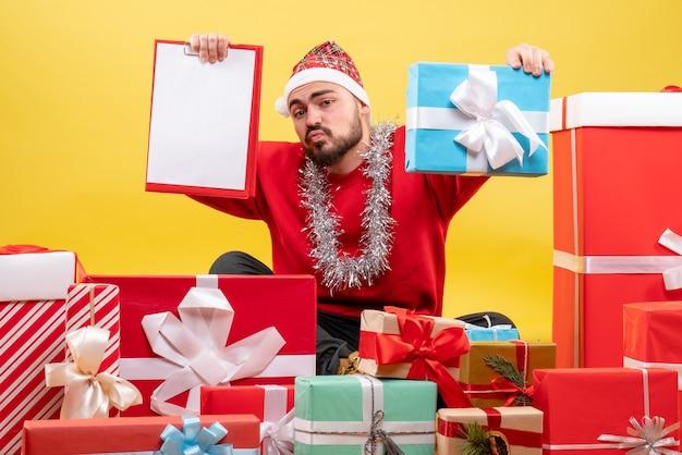 Vue de face jeune homme assis autour de cadeaux avec note sur fond jaune
