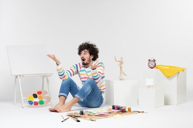 Vue de face d'un jeune homme assis autour de peintures et de dessins sur un mur blanc