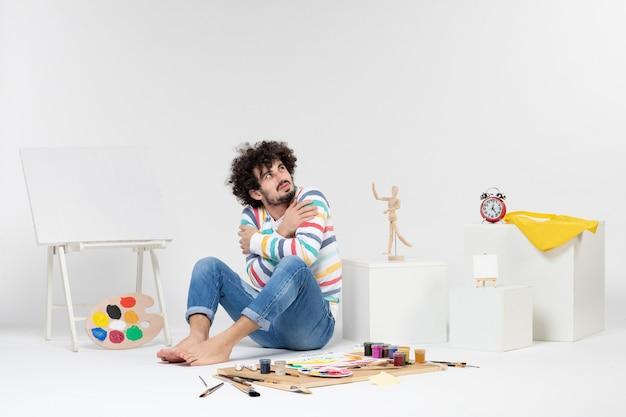 Vue de face d'un jeune homme assis autour de peintures et de dessins tremblant sur un mur blanc