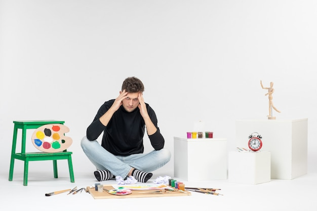 Vue de face jeune homme assis autour de peintures et de glands pour le dessin stressé sur un mur blanc dessiner une image en couleur peinture artiste peinture art