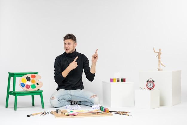 Vue de face jeune homme assis autour de peintures et de glands pour dessiner sur le mur blanc art dessiner peinture artiste couleur
