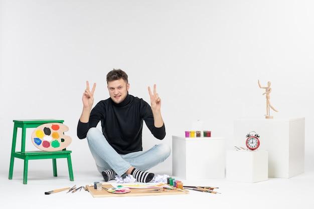 Vue de face jeune homme assis autour de peintures et de glands pour dessiner sur un mur blanc dessiner une image couleur artiste peint peinture