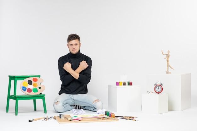 Vue de face jeune homme assis autour de peintures et de glands pour dessiner sur un mur blanc dessiner une image couleur peinture artiste peint art