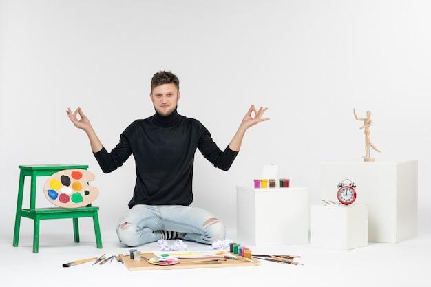 Vue de face jeune homme assis autour de peintures et de glands pour dessiner sur un mur blanc dessiner une image couleur peinture artiste peinture art