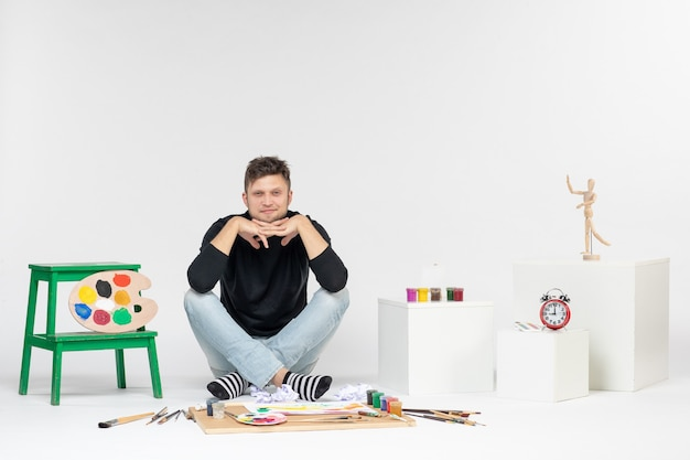 Vue de face jeune homme assis autour de peintures et de glands pour dessiner sur un mur blanc dessiner des images en couleur artiste peinture art peinture