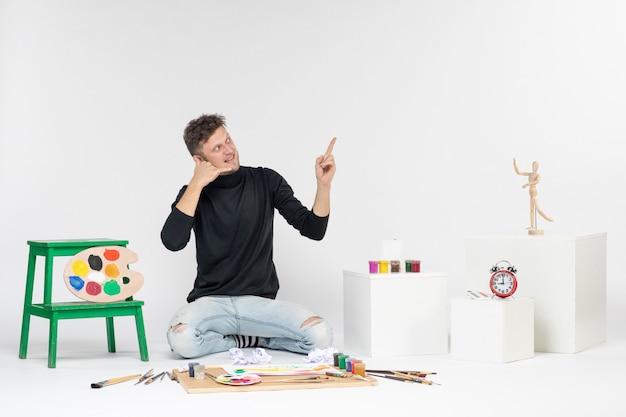 Vue de face jeune homme assis autour de peintures et de glands pour dessiner sur un mur blanc photo couleur peintures art peinture artiste dessiner