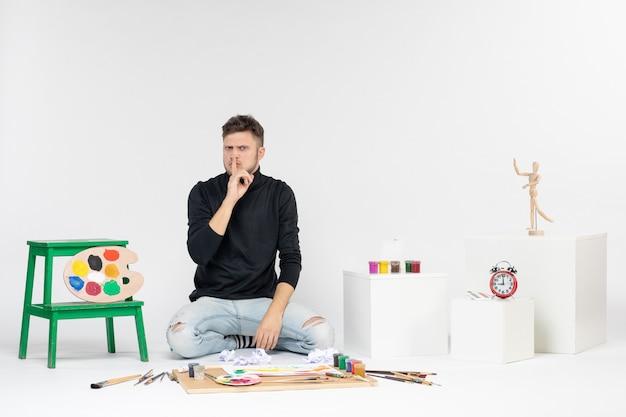 Vue de face jeune homme assis autour de peintures et de glands pour dessiner sur des peintures de couleur de mur blanc artiste dessiner la peinture d'art