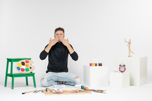 Vue de face jeune homme assis autour de peintures et de glands pour dessiner sur des peintures murales blanches artiste d'art dessiner une peinture en couleur