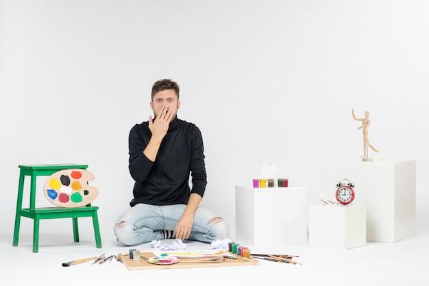 Vue de face jeune homme assis autour de peintures et de glands pour dessiner surpris sur un mur blanc artiste de peinture de couleur dessiner la peinture d'art
