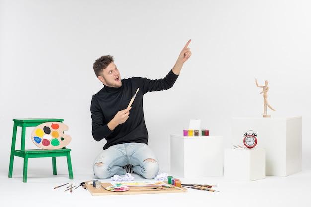 Vue de face jeune homme assis autour de peintures tenant un gland pour dessiner sur un mur blanc dessiner une image peinture peinture couleurs artiste