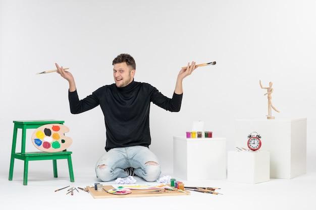 Vue de face jeune homme assis autour de peintures tenant des glands pour dessiner sur un mur blanc peinture photo dessiner artiste couleurs peintures art
