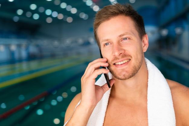 Vue de face jeune homme au bord de la piscine, parler au téléphone
