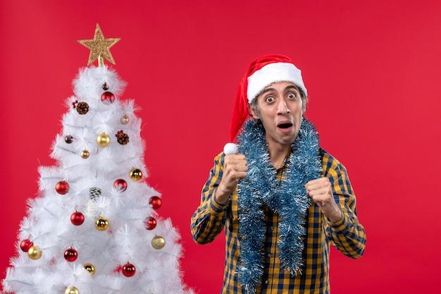 Vue de face jeune homme autour de l'atmosphère du nouvel an sur le mur rouge vacances noël humain