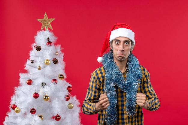 Vue de face jeune homme autour de l'atmosphère du nouvel an sur le plancher rouge émotion vacances noël