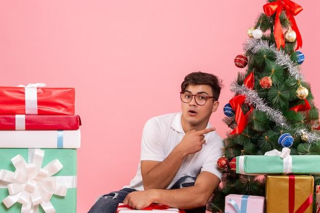 Vue de face jeune homme autour de cadeaux et arbre de noël sur le fond rose