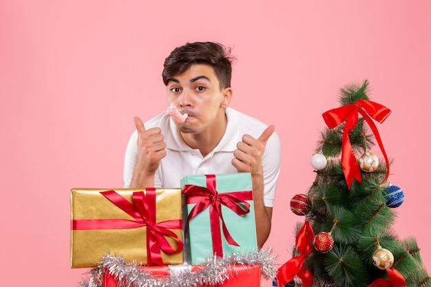 Vue de face jeune homme autour des cadeaux de noël et arbre de vacances sur le fond rose