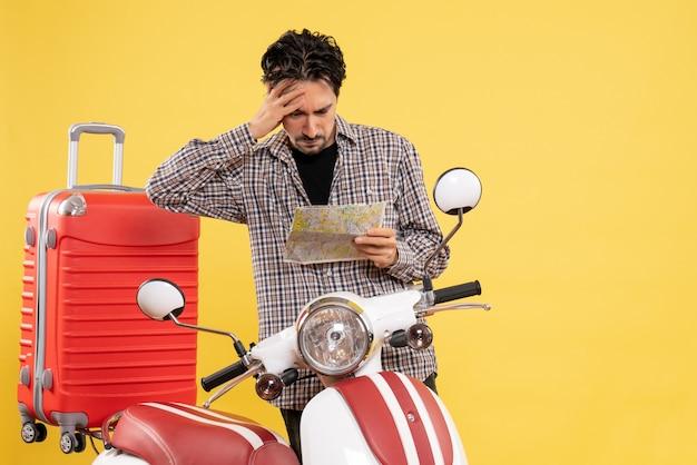 Vue de face jeune homme autour de la carte d'observation de vélo sur fond jaune voyage de vacances sur route voyage moto