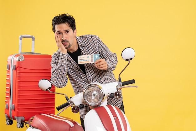 Vue de face jeune homme autour d'un vélo tenant un billet sur fond jaune road trip vacances moto voyage