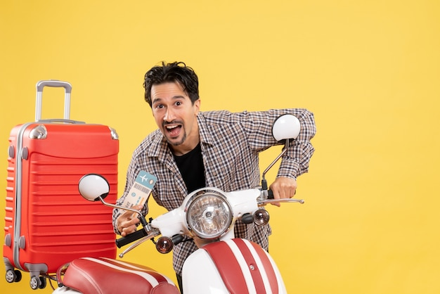 Vue de face jeune homme autour de vélo tenant un billet sur fond jaune voyage vacances voyage moto voyage