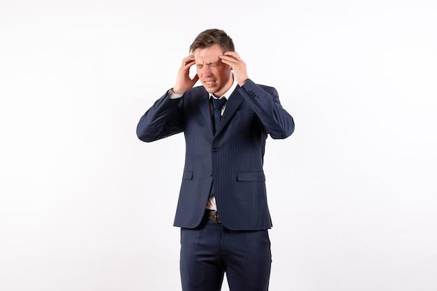 Vue de face jeune homme ayant de graves maux de tête en costume strict classique sur fond blanc émotions modèle de mode humaine costume masculin