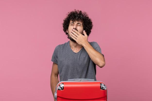 Vue de face jeune homme bâillant sur un espace rose