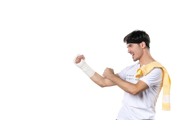 Vue de face jeune homme avec un bandage sur sa main blessée sur fond blanc athlète gym régime sport douleur blessure hôpital corps en forme de vie