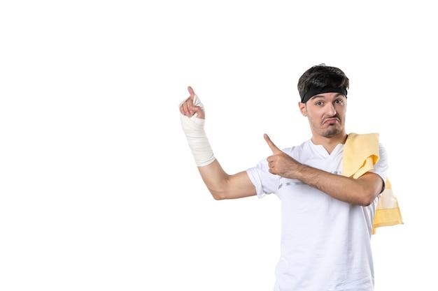 Vue de face jeune homme avec un bandage sur sa main blessée sur fond blanc régime alimentaire douleur blessure fit athlète gym corps de l'hôpital