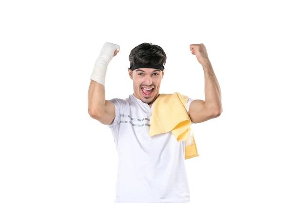 Vue de face jeune homme avec un bandage sur sa main blessée sur fond blanc régime sport douleur gym style de vie blessure fit athlète