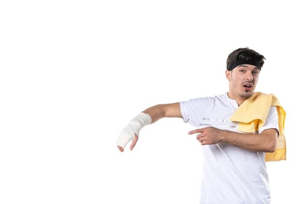 Vue de face jeune homme avec un bandage sur sa main blessée sur fond blanc régime sport douleur style de vie blessure corporelle athlète gym hôpital