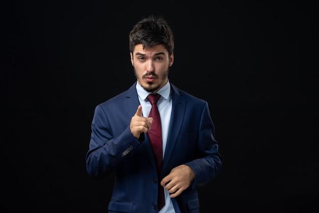 Vue de face d'un jeune homme barbu insatisfait pointant quelque chose vers l'avant sur un mur sombre isolé