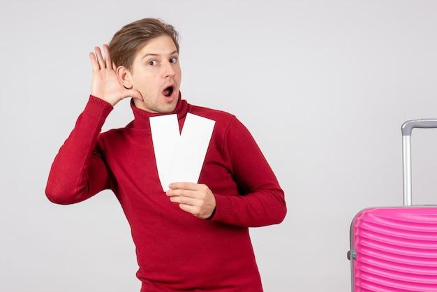 Vue de face jeune homme avec des billets d'avion sur fond blanc vacances vacances mer vacances couleur d'été