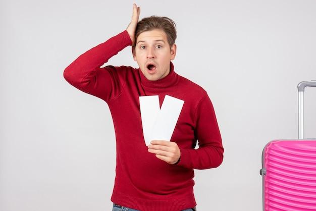 Vue de face jeune homme avec des billets d'avion sur fond blanc