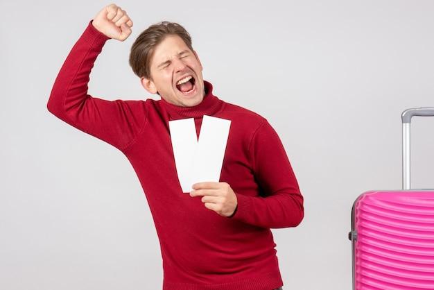 Vue de face jeune homme avec des billets d'avion se réjouissant sur fond blanc