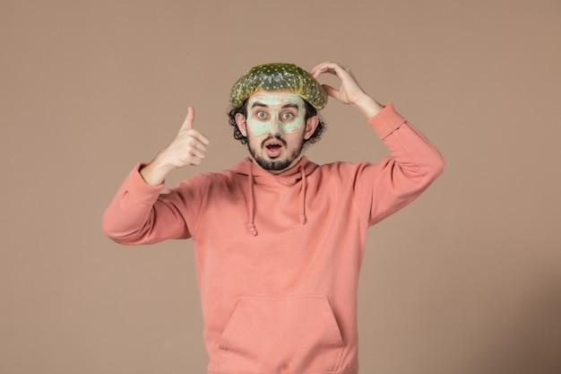 Vue de face jeune homme avec bonnet bouffant et masque sur son visage sur fond marron peau spa salon de coiffure thérapie faciale