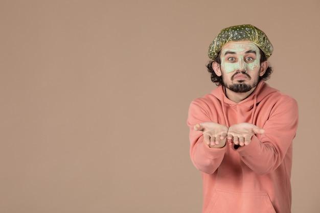 Vue de face jeune homme avec bonnet bouffant et masque sur son visage sur fond marron thérapie peau cheveux soins de la peau salon spa facial