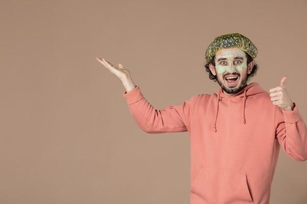 Vue de face jeune homme avec bonnet bouffant et masque sur son visage sur fond marron thérapie peau spa cheveux salon de soins de la peau massage du visage